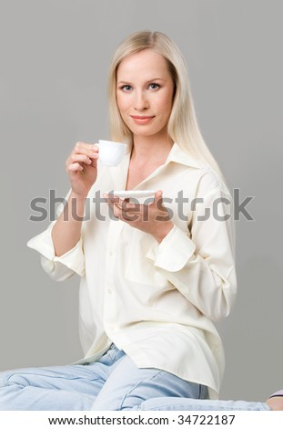 Beautiful blonde with cup of coffee looking at camera over grey background