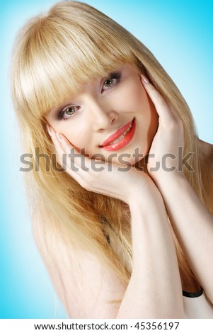 Beautiful blonde with hands on cheek over light blue background - stock photo