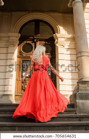 beautiful blonde with luxurious hair in a red dress is walking around the old castle