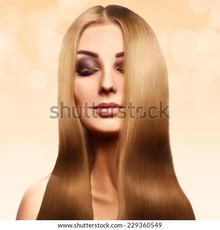 Beautiful blonde with perfect healthy long hair with professional make up in studio on abstract yellow background - stock photo