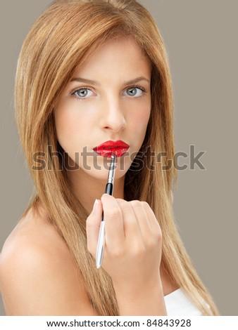 beautiful blonde woman applying red lipstick - stock photo