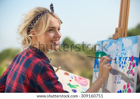 Beautiful blonde woman artist paints a colorful picture. - stock photo