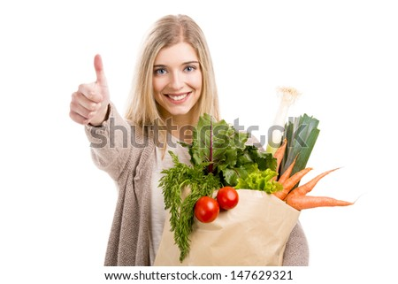Beautiful blonde woman carrying a bag full of vegetables with thumbs up, isolated over white background - stock photo