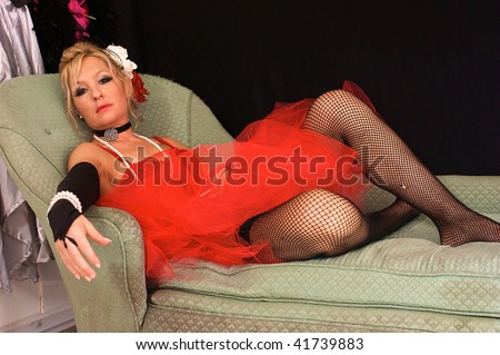 beautiful blonde woman dressed up as old fashioned madam or prostitute, could also be a sexy elf or mrs. claus for christmas, looking directly at viewer.  Shot with blue and red strobes. - stock photo