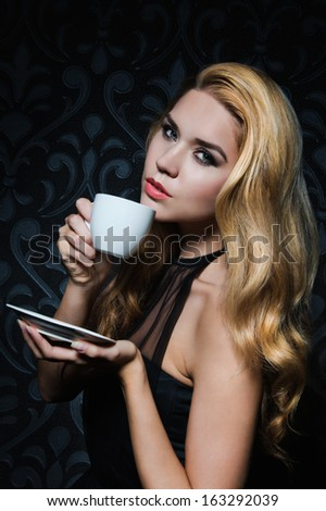 Beautiful Blonde Woman enjoying a cup of Coffee.Isolated on black background - stock photo