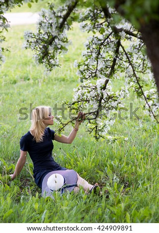 Beautiful blonde woman head and shoulders portrait in a flowered spring garden, wearing big white and blue hat.Youth and beauty.Flowers of Spring. Spring flowers.  - stock photo