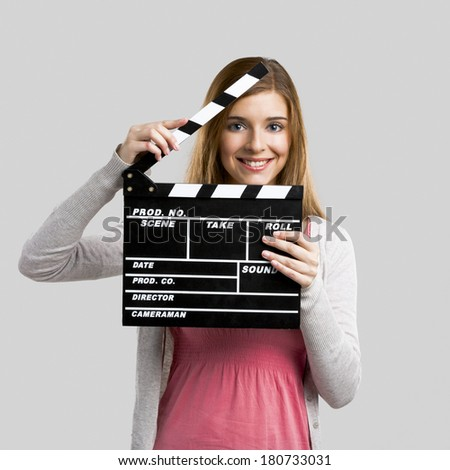 Beautiful blonde woman holding  a clapboard, isolated over gray background - stock photo