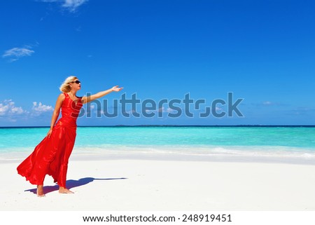 Beautiful , blonde woman in a red dress with an arm raised at Maldives beach.Copy space - stock photo