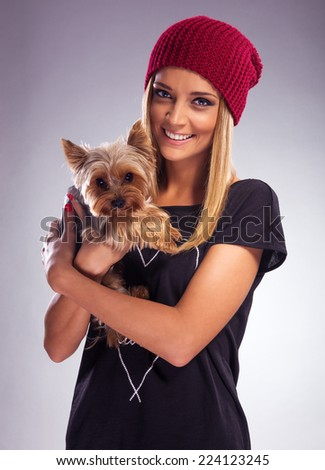 Beautiful blonde woman in autumn dress, holding a yorkshire terrier dog - stock photo