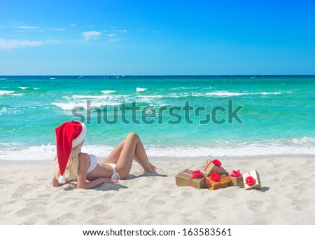 Beautiful blonde woman in bikini, red christmas hat and many gift boxes on sea beach. New year holidays in hot countries concept - stock photo