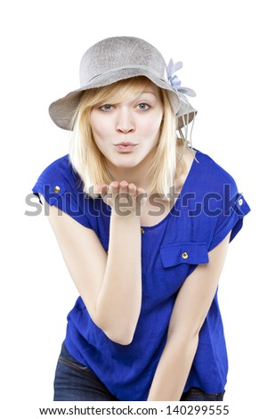 Beautiful blonde woman in casual attire with hat blowing a kiss against white background