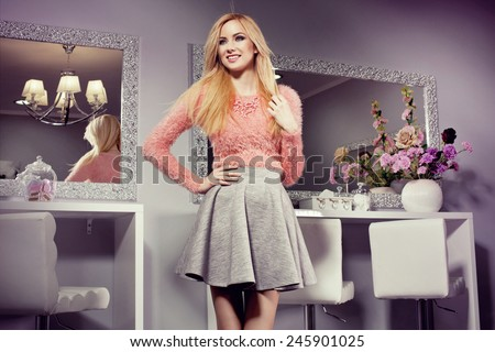 beautiful blonde woman in grey skirt and pink fluffy sweater at beauty salon. Nice interior