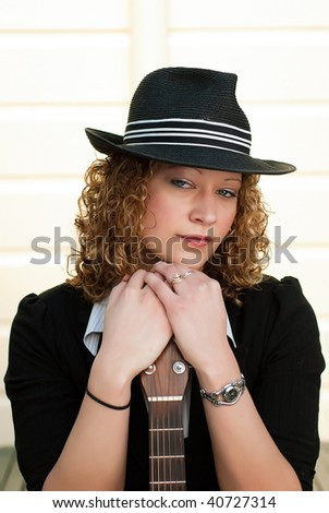 Beautiful blonde woman in hat posing with a guitar - stock photo