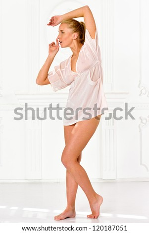 Beautiful blonde woman  in lingerie in white interior. - stock photo