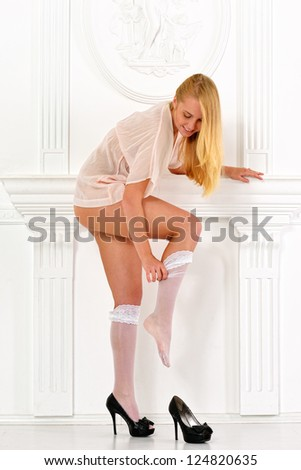 Beautiful blonde woman  in lingerie in white interior. Studio shooting. - stock photo