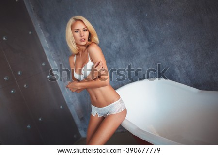 beautiful blonde woman in lingerie is sitting on the edge of the red bathroom in the Studio