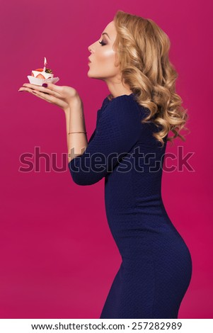 Beautiful blonde woman in luxury blue dress and curly hairstyle blowing candle on birthday cake. clear skin. pink background - stock photo