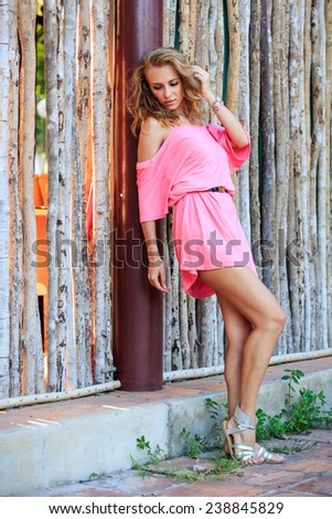 Beautiful Blonde Woman In Pink Dress Posing In The Park - stock photo