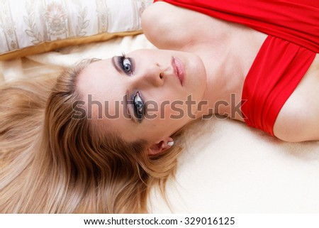 Beautiful blonde woman in red dress on the bed