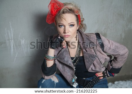 Beautiful blonde woman in rock style sits at concrete wall and looking at the camera - stock photo