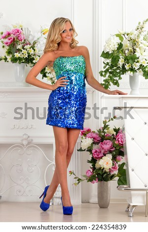 Beautiful blonde woman in short blue gown dress. Studio with luxury interior with  flowers. - stock photo