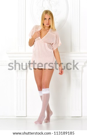 Beautiful blonde woman in studio with white antique background. She is dressed in white lingerie and stockings. - stock photo