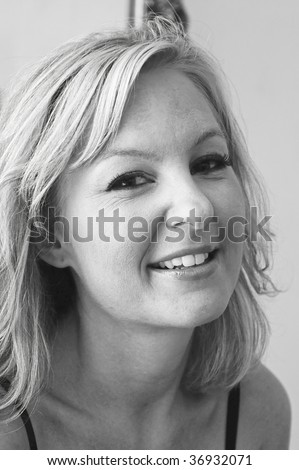 beautiful blonde woman is looking at viewer with a smile and her head tilted back slightly , black and white image - stock photo
