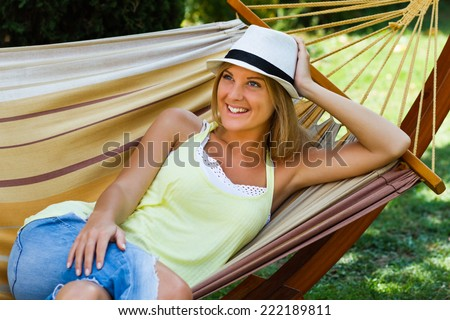 Beautiful  blonde woman is lying on hammock and enjoy in her free time.Leisure time - stock photo