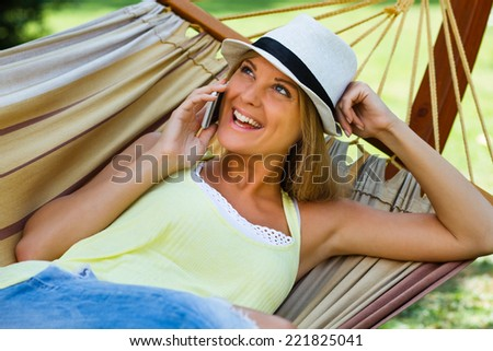 Beautiful  blonde woman is lying on hammock and using mobile phone.Using mobile phone - stock photo