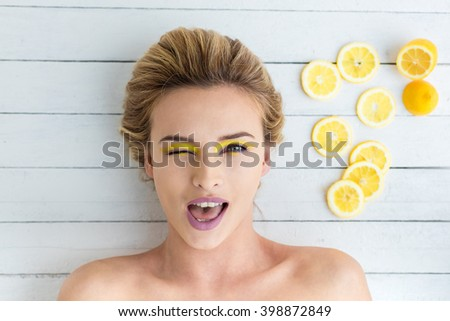 beautiful blonde woman laying on a white wooden background next to slices of lemon  - stock photo