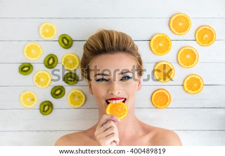 beautiful blonde woman laying on a white wooden table next to slices of orange, lemon and kiwi. Taking a bite - stock photo