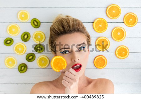beautiful blonde woman laying on a white wooden table next to slices of orange, lemon and kiwi - stock photo