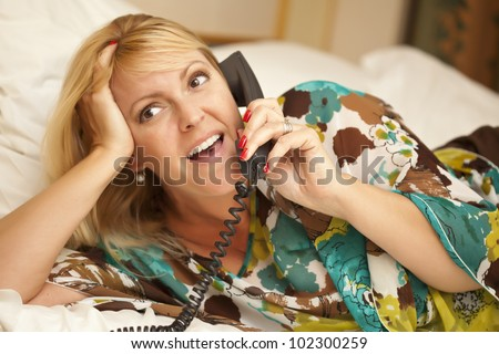 Beautiful Blonde Woman Laying on Her Bed Using the Telephone. - stock photo