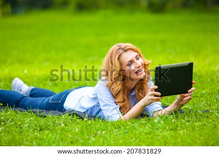beautiful blonde woman lying in grass and using a tablet