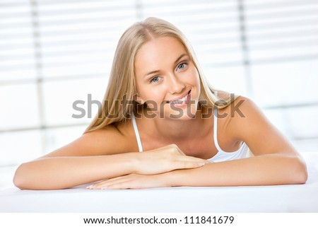 Beautiful blonde woman lying on the bed and smiling - stock photo