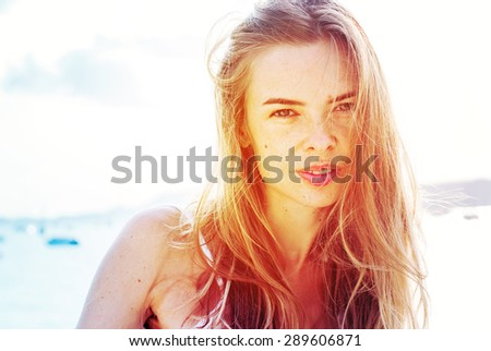 Beautiful Blonde Woman On the Background Before Blue Sea in Sunrise. Summer day - stock photo
