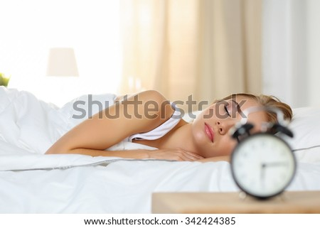 Beautiful blonde woman peacefully lying in bed sleeping early morning while alarm clock going to ring awakening. Early wake up, not getting enough sleep, oversleep, getting work time concept - stock photo