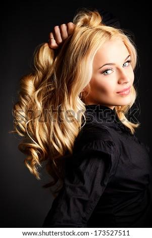 Beautiful blonde woman posing at studio over black background. - stock photo