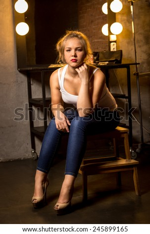 Beautiful blonde woman posing on chair at theater dressing room