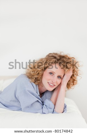 Beautiful blonde woman posing while lying on her bed in her apartment - stock photo