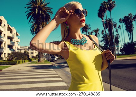 beautiful blonde woman posing with handbag in yellow dress and sunglasses among palm trees. Fashion photo