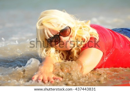 Beautiful blonde woman  relaxing on sunny perfect white sand beach  during summer travel. Luxury getaway vacation. Nice waves - stock photo