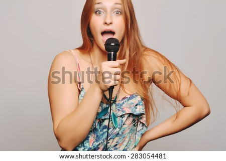 Beautiful blonde woman singing with microphone. Music concept - stock photo