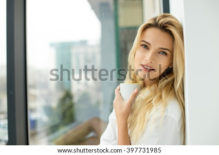 beautiful blonde woman sitting comfortably on a balcony, wearing men's shirt holding a coffee