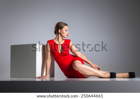Beautiful blonde woman sitting in red dress by white cube over the gray background.  - stock photo