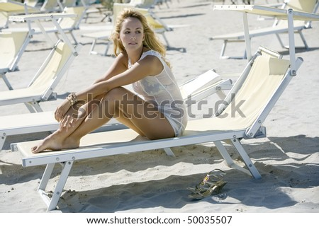 Beautiful blonde woman sitting on a deck chair wearing a white sundress - stock photo
