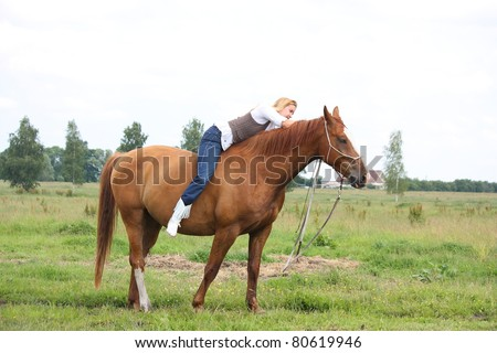 Beautiful blonde woman sitting on chestnut horse without saddle at the field