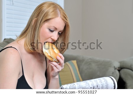 Beautiful blonde woman sitting on couch in black tank and sweat pants reading a paper and eating a bagel with cream cheese - biting into bagel - stock photo