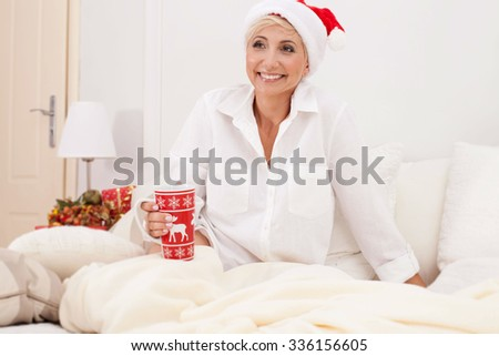 Beautiful blonde woman sitting on the bed in santa claus hat. Christmas time. - stock photo