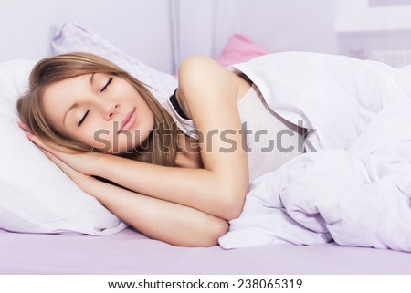Beautiful blonde woman sleeping in her bed in pajamas, smiling - stock photo